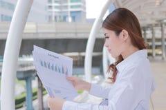 Взгляд со стороны привлекательной молодой азиатской бизнес-леди анализируя обработку документов или диаграммы в ее руках на внешн Стоковые Изображения RF