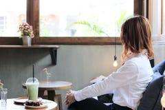 Взгляд со стороны привлекательной молодой азиатской женщины смотря через окна в кофейне Стоковое фото RF