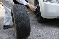 Взгляд со стороны профессионального автомобильного человека механика в равномерной держа автошине для фиксируя автомобиля на пред Стоковое фото RF