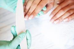 Новый маникюр Взгляд со стороны процесса маникюра в салоне Профессиональный manicurist снабжает обслуживание клиент стоковое фото