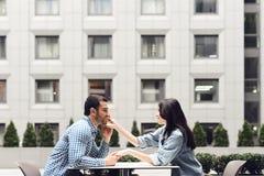 Взгляд со стороны Романтичные пары сидя в кафе стоковая фотография