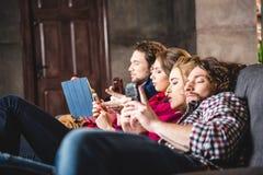 Взгляд со стороны серьезных друзей используя цифровые приборы стоковые фото