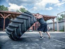Взгляд со стороны сильного мышечного человека фитнеса двигая большую автошину в спортзале улицы Концепция поднимаясь, тренировка  стоковые изображения rf