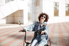 Взгляд со стороны смеясь над девушки в солнечных очках представляя на мотоцилк Стоковые Изображения RF