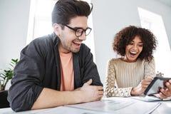 Взгляд со стороны смеяться молодыми коллегами имея потеху совместно стоковое изображение