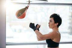 Взгляд со стороны снял груши бокса бойца боевых искусств поразительной малой Стоковая Фотография