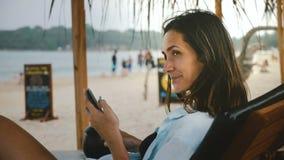 Взгляд со стороны снятый молодой счастливой усмехаясь туристской женщины с напитком и смартфона отдыхая, смотрящ вокруг в шезлонг видеоматериал
