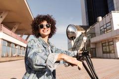 Взгляд со стороны счастливой девушки в солнечных очках представляя на мотоцилк Стоковое фото RF