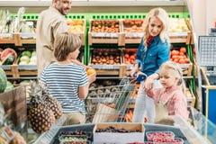 взгляд со стороны счастливой молодой семьи при 2 дет ходя по магазинам совместно Стоковые Изображения