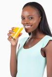 Взгляд со стороны сь женщины с апельсиновым соком Стоковые Изображения RF