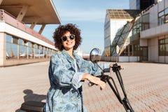 Взгляд со стороны усмехаясь девушки в солнечных очках представляя на мотоцилк Стоковое Изображение RF