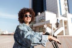 Взгляд со стороны усмехаясь девушки в солнечных очках представляя на мотоцилк Стоковая Фотография