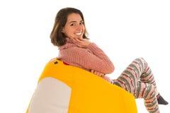 Взгляд со стороны усмехаясь милой женщины сидя на желтом стуле погремушкы стоковое фото