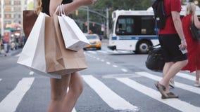 Взгляд со стороны хозяйственных сумок нося анонимной молодой женщины пока пересекающ улицу в замедленном движении Нью-Йорка акции видеоматериалы