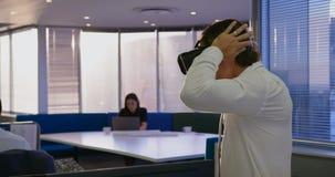 Взгляд со стороны шлемофона виртуальной реальности молодой кавказской мужской исполнительной власти нося в современном офисе 4k видеоматериал