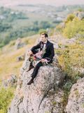 Взгляд со стороны groom сидя на утесе и держа огромный букет красочных цветков стоковое фото rf