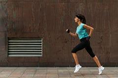 Взгляд со стороны sporty молодой женщины бежать на тротуаре стоковые изображения rf