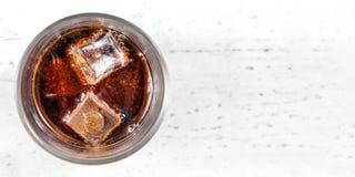 Взгляд столешницы, стекло с напитком колы и кубы льда на белой доске Широкое фото, космос для права текста стоковые фото