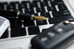 Взгляд столешницы стола офиса отсутствие людей с компьтер-книжкой, блокнотом, ручкой, приводом ручки, ключами автомобиля, черной  стоковое фото