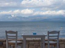Взгляд террасы с деревянной серой таблицей и 2 серыми стульями, морем, cl стоковое изображение