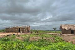 Взгляд традиционной деревни, людей и листа покрыванного соломой и цинка на домах крыши и терракотовых кирпичных стенах стоковое изображение rf