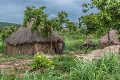 Взгляд традиционной деревни, приветствие детей на покрыванном соломой доме со стенами крыши и терракоты и соломы стоковое изображение rf