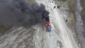 Взгляд трутня горя автомобиля с большим пламенем и огромного дыма в дезертированном поле пыли акции видеоматериалы