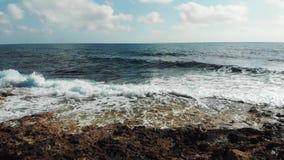 Взгляд трутня сильных волн моря ударяя против скалистого пляжа Скалистый seashore с волнами ударяя создающ пену и брызгать сток-видео