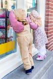 Взгляд украдкой марионетки мальчика и девушки через окно магазина Стоковые Фотографии RF