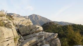 Взгляд урожая женщины идет с рюкзаком на скале горы против красивого пика гор видеоматериал