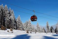 Взгляд фуникулера, снежных спрусов и горнолыжного склона на солнечном da стоковые фотографии rf