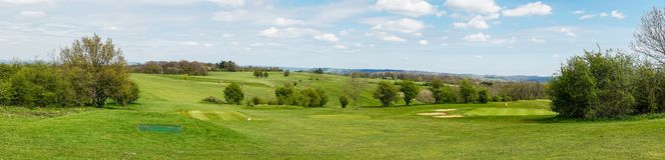 Взгляд холма и поля для гольфа Stinchcombe как осмотрено от следа пути Cotswold национального стоковые фото