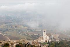 Взгляд церков Св.а Франциск Св. Франциск папской в Assisi Умбрии, Италии в середине поднимаясь тумана утра стоковое фото