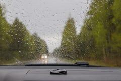 Взгляд через влажное стекло в автомобиле на дороге на дождливый день стоковое фото rf