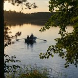 Взгляд через деревья на озере со шлюпкой и небом захода солнца стоковые фотографии rf
