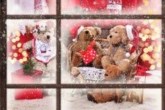 Взгляд через окно к семье плюшевого медвежонка на времени рождества Стоковая Фотография