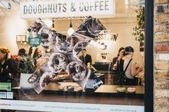 Взгляд через окно людей внутри Crosstown донутов и кафа кофе в рынке Гринвич, Лондоне, Великобритании стоковое фото