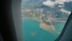 Взгляд через окно самолета на тропических острове, океане, море, небе и облаках Море, облака и небо вида с воздуха как сток-видео