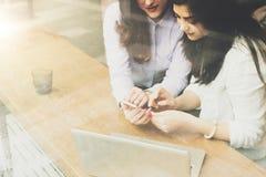Взгляд через стекло 2 девушки сидя в кафе на таблице перед компьтер-книжкой, используя smartphone Онлайн маркетинг, образование Стоковое фото RF