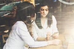 Взгляд через стекло 2 девушки сидя в кафе на таблице перед компьтер-книжкой, используя smartphone Онлайн маркетинг, образование Стоковые Изображения RF