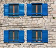 Взгляд ярких голубых деревянных окон и штарок на среднеземноморском старом каменном доме в Хорватии Стоковое Фото