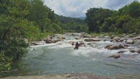 Взгляд Fisher трутня падает сеть в отмелое реку среди речных порогов акции видеоматериалы