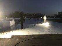 Взгляд nighttime Roofers извлекая доработанный лист крышки от коммерчески плоской крыши для преобразования к TPO с безопасностью  Стоковая Фотография