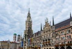 Взгляд Rathaus или здание муниципалитета на главной площади Marienplatz в Мюнхене, Германии с башнями церков на заднем плане Стоковая Фотография