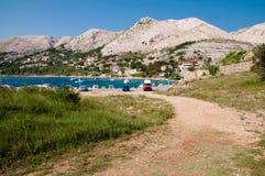 Взгляд Stara Baska от маленькой грязной улицы на krk - Хорватии Стоковые Изображения RF