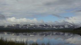 Взгляд Timelapse озера горы с красивыми облаками отраженными в поверхности воды сток-видео
