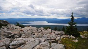 Взгляд Zyuratkul России - июля 2015 озера Zyuratkul от вершины горы Zyuratkul в пасмурной погоде стоя на камнях стоковое изображение rf