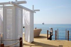 Взгляд белого шатра пляжа, корабля и голубого моря в гостинице Стоковая Фотография