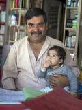 Взгляд бизнесмена в передний усмехаться, держит его младенца, сидит на бакалейной лавке Стоковая Фотография