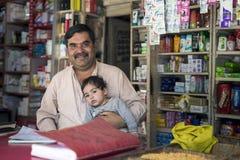 Взгляд бизнесмена в передний усмехаться, держит его младенца, сидит на бакалейной лавке Стоковые Изображения RF